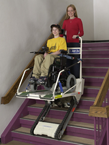 woman using the Garaventa Super-trac to evacuate a young man down the stairs