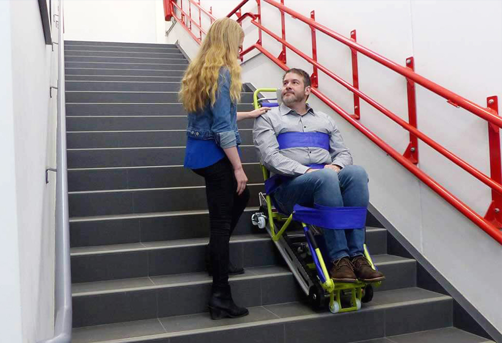 blonde woman is evacuation a guy with an emergency wheelchair through the stairs