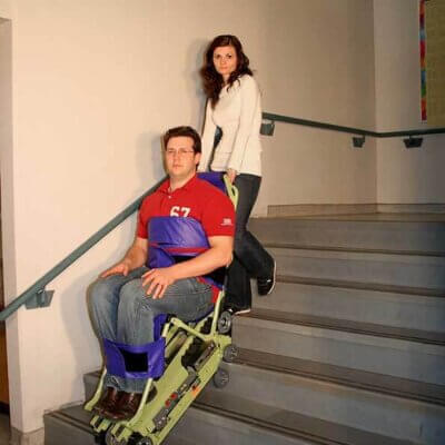 woman using the powertrac on the stairs with a guy sitting on it