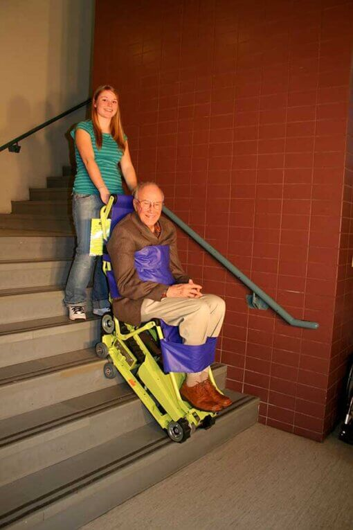 woman using the powertrac chair with an old male sitting on it