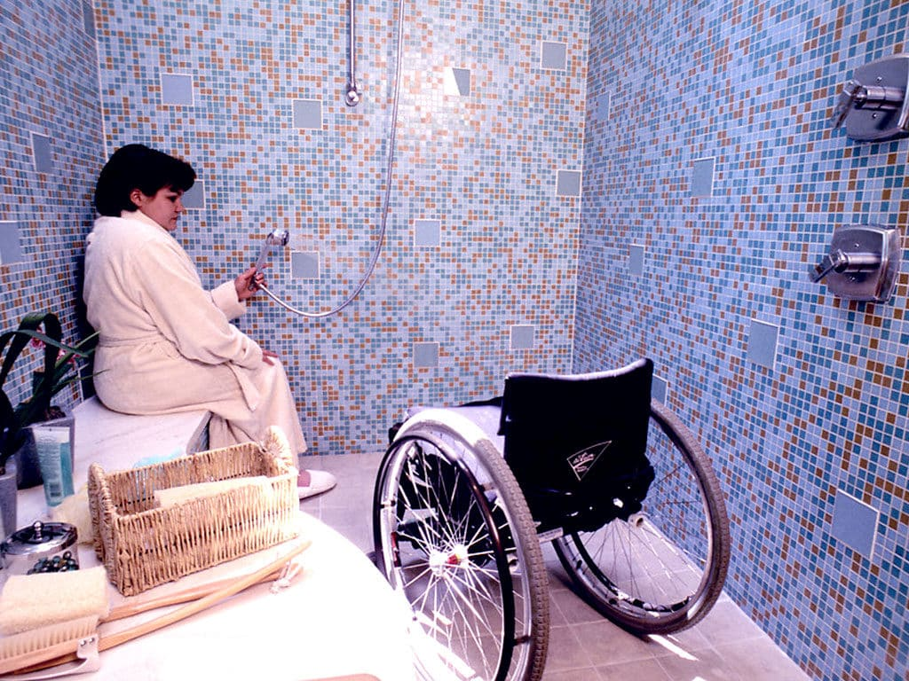 Woman with a robe in a shower next to a wheelchair