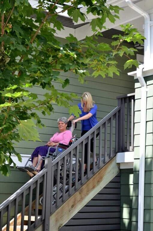 woman using the stairtrac on the stairs of her house